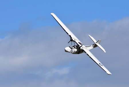 """ICKWELL, BEDFORDSHIRE, ENGLAND - SEPTEMBER 06, 2020: Vintage PBY-5A Catalina """"Miss Pick Up� (G-PBYA) Flying Boat  in Flight."""