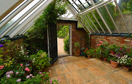 TICEHURST, EAST SUSSEX, ENGLAND - MAY 18, 2019: Old Greenhouse interior with plants and flowers.