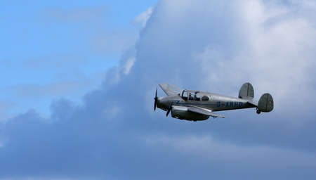 ICKWELL, BEDFORDSHIRE, ENGLAND - SEPTEMBER 06, 2020: Vintage   Miles M65 Gemini, G-AKHP  aircraft  in Flight  against cloudy sky.