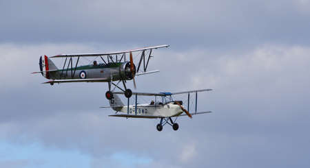 ICKWELL, BEDFORDSHIRE, ENGLAND - SEPTEMBER 06, 2020: Vintage De Havilland  1928  DH60X  Moth biplane and  Avro 621 Tutor biplane Aircraft in flight cloudy sky. Editorial