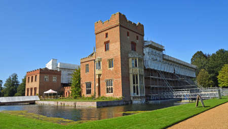 OXBOROUGH, NORFOLK, ENGLAND - SEPTEMBER 19, 2020: Oxburgh Hall under going roof repairs with scaffolding  and moat. Editorial