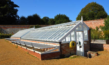 AYLSHAM, NORFOLK, ENGLAND - SEPTEMBER  21, 2020:  Traditional Green houses with trees and blue sky in background.