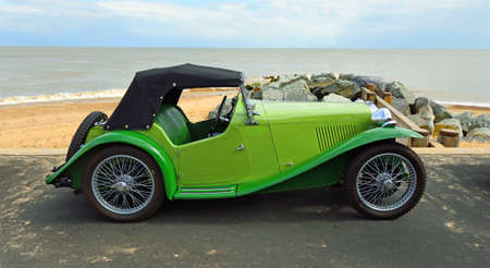 FELIXSTOWE, SUFFOLK, ENGLAND - MAY 05, 2019: Classic  Green MG  Sports Car parked on seafront promenade with beach and sea in background. Editorial