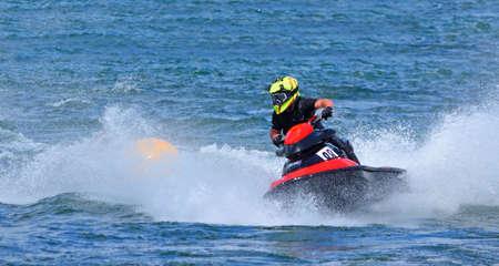 Jet Ski  racer creating at lot of spray black and red jet-ski