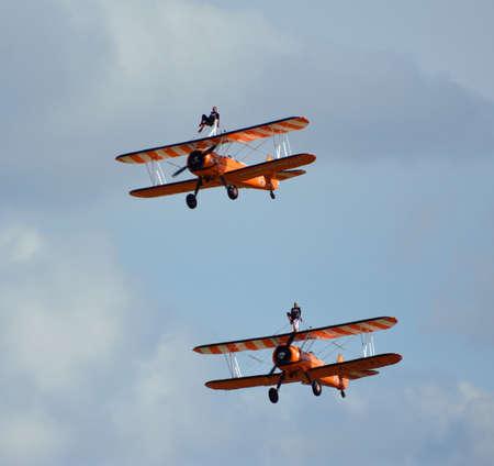 ICKWELL, BEDFORDSHIRE, ENGLAND - AUGUST 02, 2020: Aerosuperbatics  wing walking display team two aeroplanes in flight.