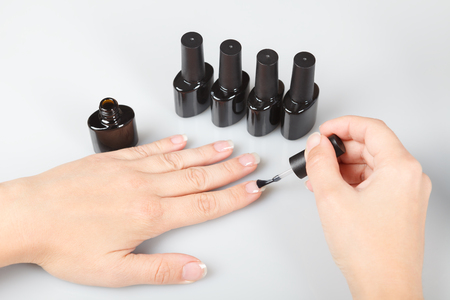 nail care. a woman covers her nails with transparent lacquer. Stock Photo