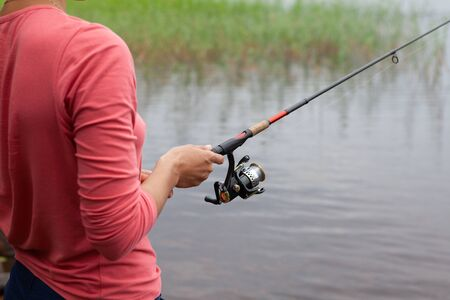 Fishing rod with a fishing reel in a womans hand