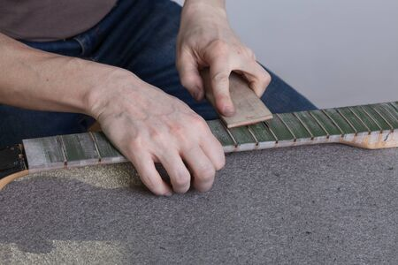 the master polishes the frets on the fretboard of the guitar. The fingerboard is protected by molar tape