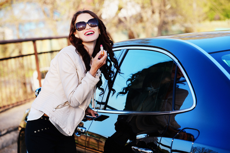Girl paints her lips near the car