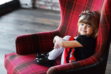 Girl sitting in red armchair at home