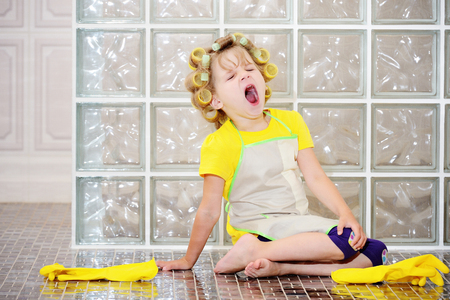 The little girl was cleaning the house. She helped my mother, she was very tired. Yawns. Wants to sleep. Stock Photo