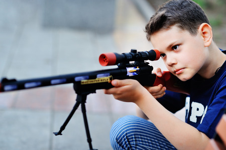 A young boy looks in the sight of a toy rifle