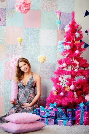 A young, beautiful girl, a future mother dressed up a tree and prepared presents. Imagens