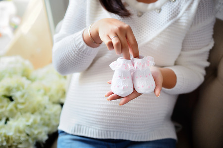 The future mother holds the booties in her hands. She is very much looking forward to the birth of her baby.