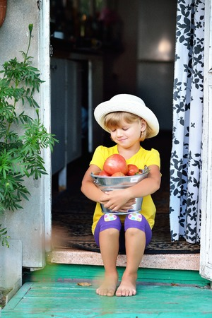 A small, pretty girl in a hat gathered a harvest of ripe red tomatoes Stock Photo