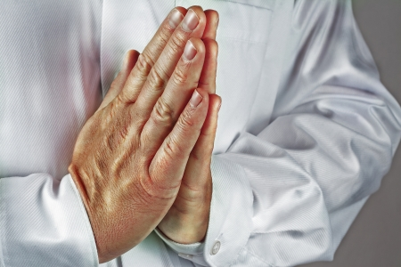 A man with praying hands and a white shirt. The Picture is made in the dragan effekt and is also toned Stock Photo
