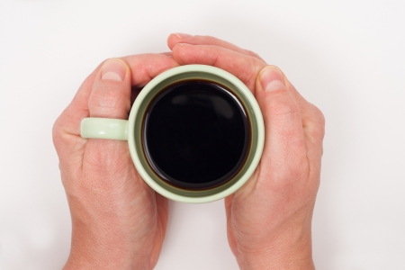Two hands hold a cup of coffee on a white table.