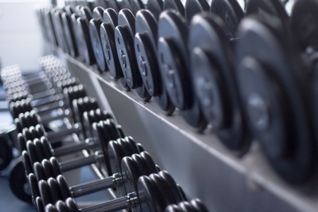 Dumb bells lined up in a fitness studio. picture is short focus Stock Photo