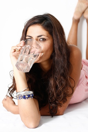 A beauty darkaired women drinks a glass of water Stock Photo - 17081765