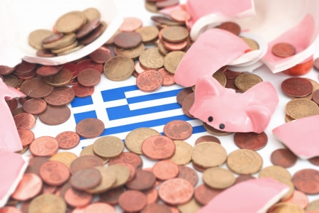 A broken Piggybank with the Flag og greece in the middle of the picture .  Its a synonyme for the finance crisis