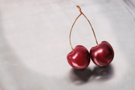 Two cherries in bright red on a stainless steel ground. picture is toned photo