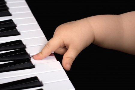 A child one year old plays with one finger piano in front of a black background