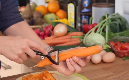 A women skin a carrot in a kitchen with some vegetables in th ebackground