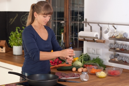 A blonde Women spice a dish with  beef filet in a kitchen with a wooden workplate