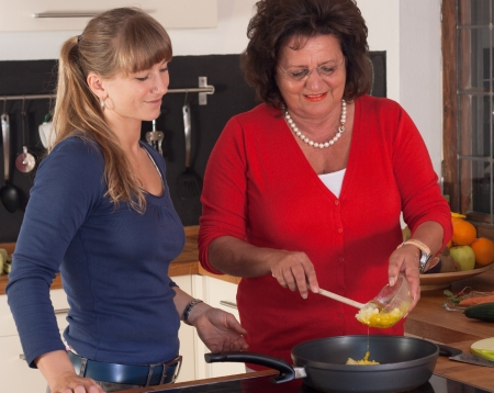25 30 years old: A older and a younger women are cooking in the kitchen