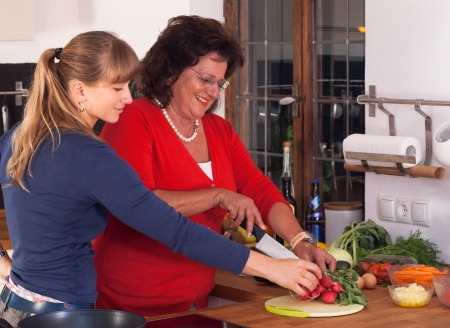 A older and a younger women tasting food in the kitchen