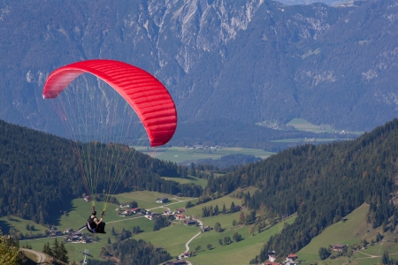 A paraglider flys in the austrian mountain. is in the startphase Stock Photo