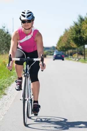 A young adult women is driving a race bike in a pink shirt and a helmet Stock Photo