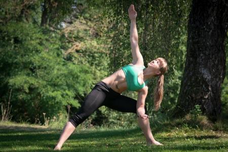 joga: A blonde women makes joga barefoot in green grass