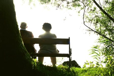 Two old Person sitting on a bank near a lake and injoy the evening sun Picture is toned