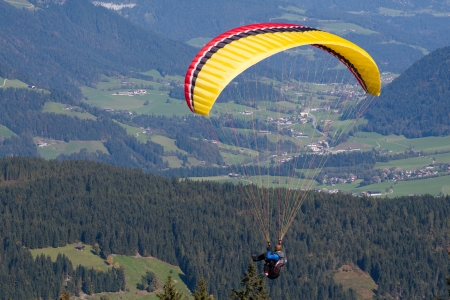 A paraglider flys in the austrian mountain  is in the startphase Stock Photo