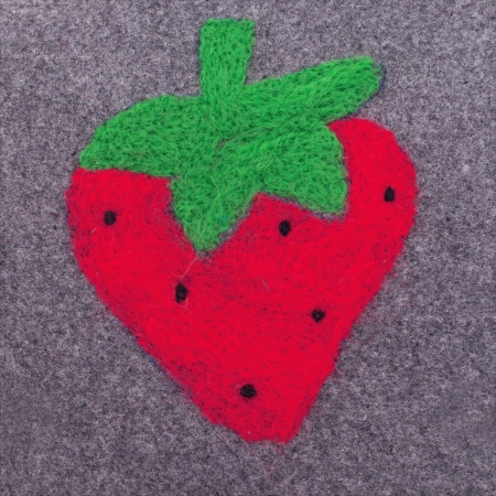 A pagefiled strawberrie on a grey stuff. Green and red Stock Photo - 17161714