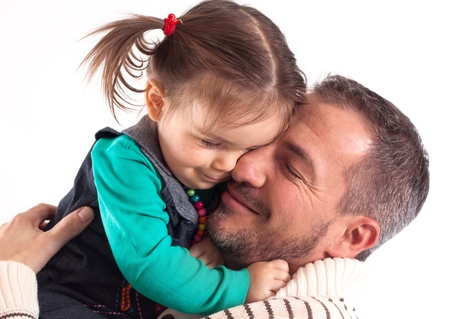 A father and a doughter together hold each other and have closed eyes. in front of white background photo