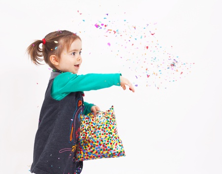 A cute girl throw confetti on the floor in front of a white background