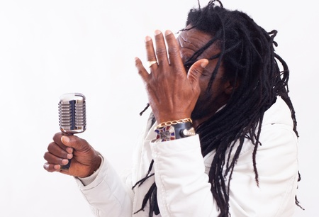 A Rasta Singer hold a micro and hide his face. Focus on Micro . Hand in Front unsharp.