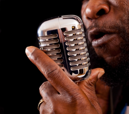 A closeup of a rasta singer with a chrome microphone