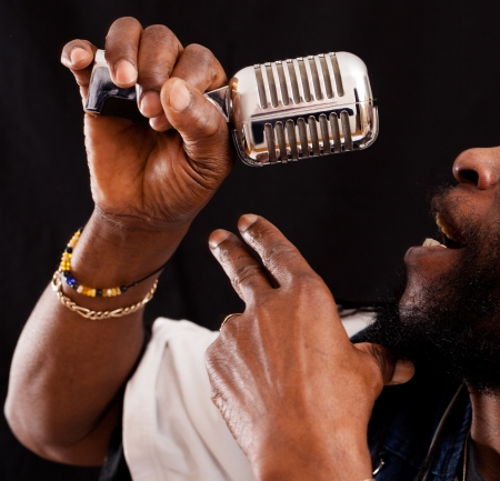 A Jazz singer hold a Micro in his Hand and Sings Stock Photo