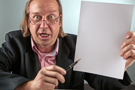 A angry looking manager hold a blank paper in his hand . picture with high contrast. picture is toned photo