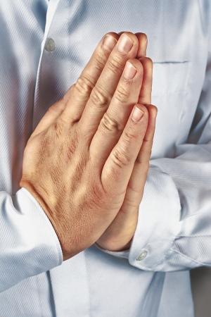 orando manos: rezando Manos de un hombre delante de una camisa blanca