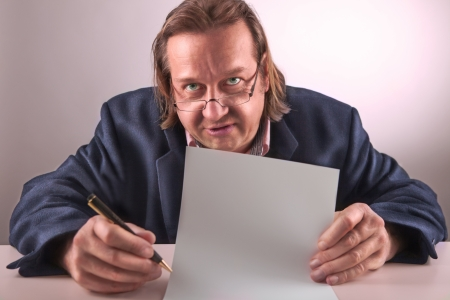 A angry looking manager hold a blank paper in his hand   picture with high contrast picture is toned photo