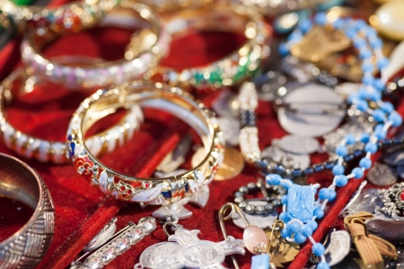 jewlery: A mount of jewlery on a market. Focus on blue jesus plate. Stock Photo