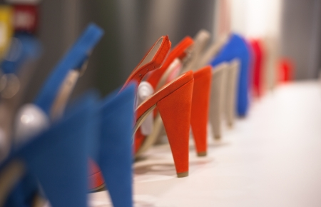 Shoes in a line , red and blue. Focus on red shoe. Short of focus.