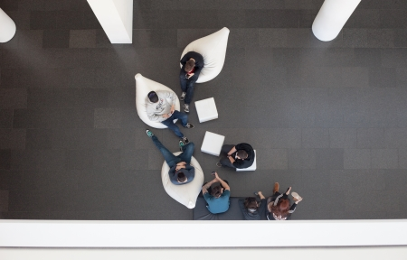 People sitting in softchairs in the Museum of Arts in Barcelona having a break and talk.And stearing in there smartphones Picture made from above. Editorial