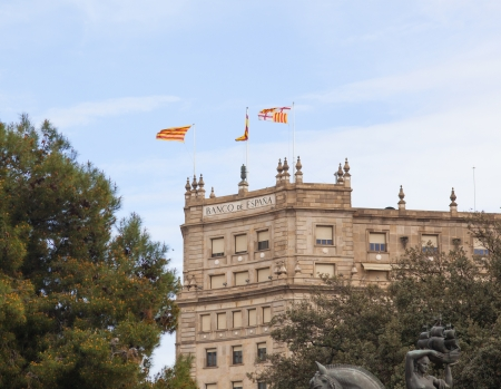 The building of the Bank of Spain with flags . Picture between trees.