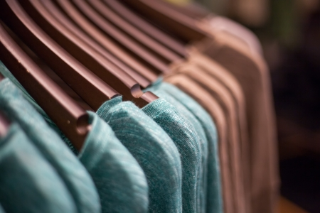 Brown and green Shirts hanging in Line on hanger. Stock Photo