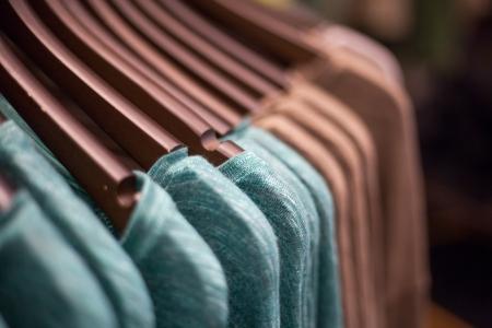 textile industry: Camisas pardas y verdes colgando en la línea en la percha.